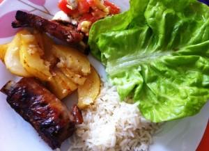 Costela de porco, batatas, arroz, alface e salada de tomate com ovos de codorna