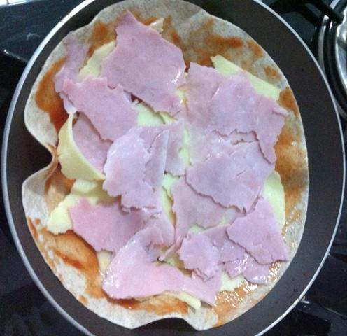 Coloque o presunto e o queijo picado sobre a pizza de frigideira
