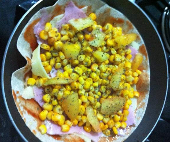 Acrescente milho, tomate, orégano e azeite na pizza de frigideira